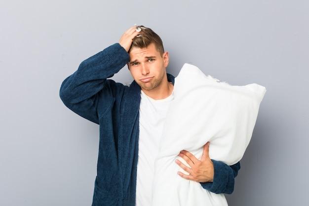 ショックを受けている枕を持ってピジャマを着ている若い男は、彼女は重要な会議を覚えています。