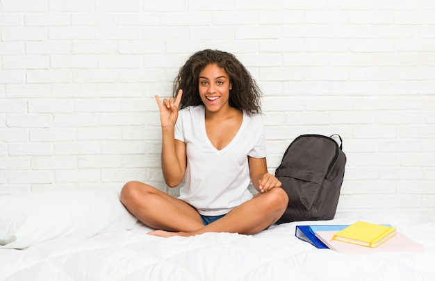 革命の概念として角ジェスチャーを示すベッドの上の若いアフリカ系アメリカ人学生女性。