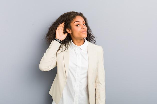 Молодая афро-американская бизнес-леди пробуя слушать сплетню.