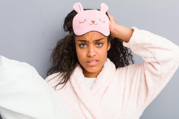 パジャマとショックを受けている枕を保持している睡眠マスクを身に着けている若いアフリカ系アメリカ人女性は、重要な会議を覚えています。