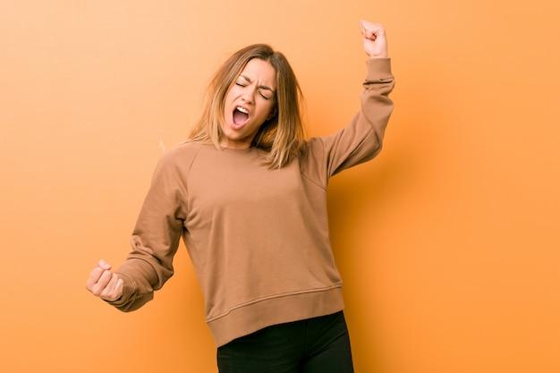 Молодая подлинная харизматическая женщина реальных людей на кулаке поднимать стены после победы, концепции победителя.