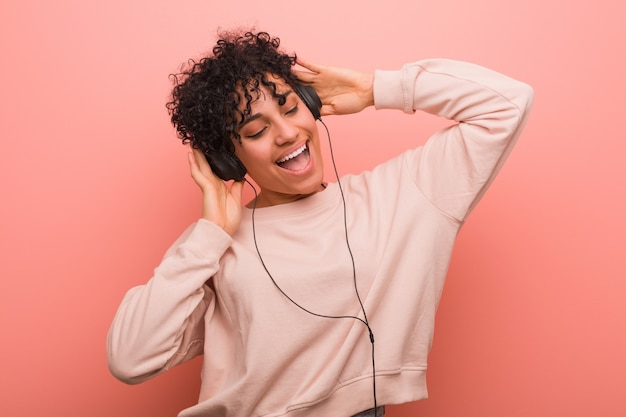 あざダンスとヘッドフォンで音楽を聴くと若いアフリカ系アメリカ人女性