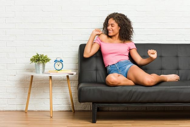 Молодая афро-американская женщина сидя на софе танцуя и имея потеху.