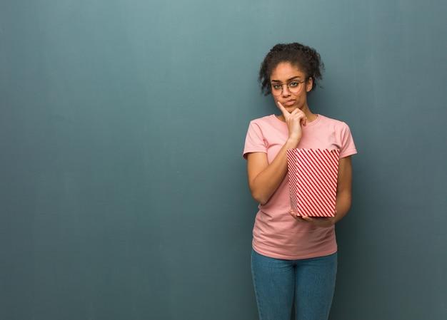 若い黒人女性の疑いと混乱。彼女はポップコーンのバケツを持っています。