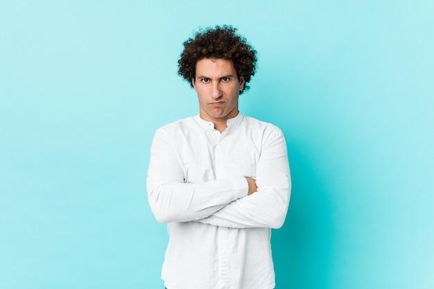 Молодой кудрявый зрелый человек, нахмурив лицо в элегантной рубашке недовольство, держит руки сложенными.