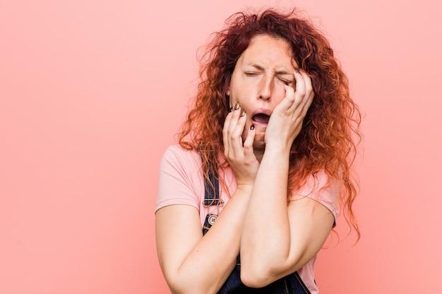 若い可愛いジンジャー赤毛の女性がジーンズダンガリーを着て泣き言を泣き叫んでいます。