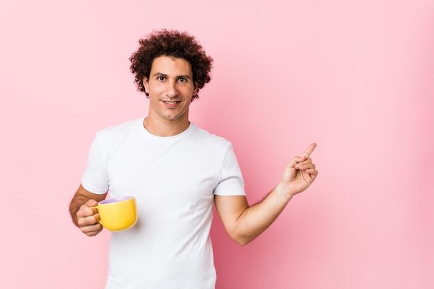 Молодой кавказской кудрявый человек, держа чашку чая, весело улыбаясь указательным пальцем прочь.
