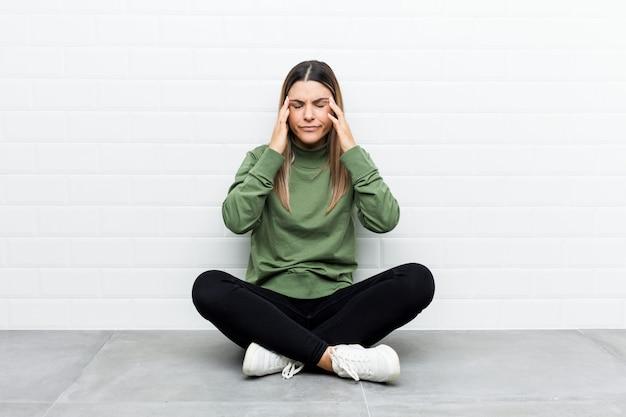Молодая кавказская женщина сидя на висках пола касающих и имея головную боль.