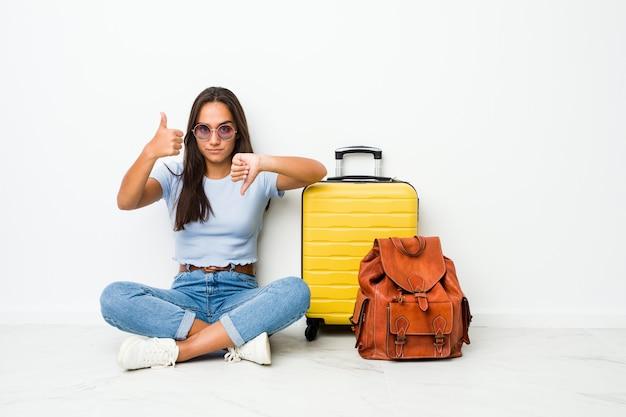 Молодая индийская женщина смешанной расы готова пойти путешествовать, показывая большие пальцы руки вверх и пальцы вниз, трудно выбрать концепцию