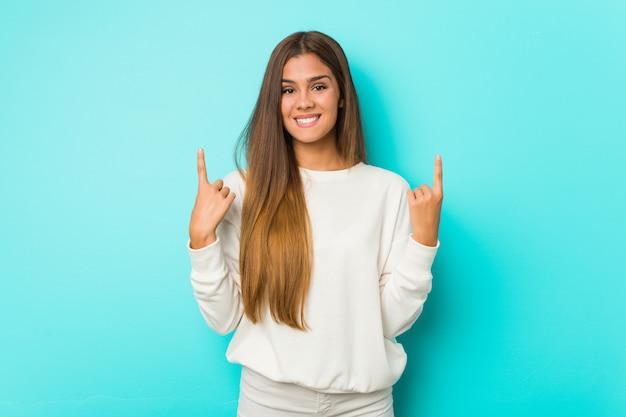 Молодая тонкая женщина указывает с обоими пальцами носа вверх показывая пустое пространство.