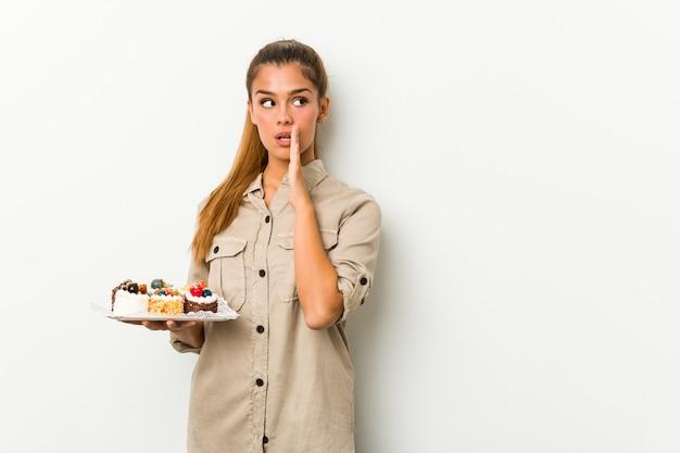 甘いケーキを保持している若い白人女性は秘密のホットなニュース速報を言っています。