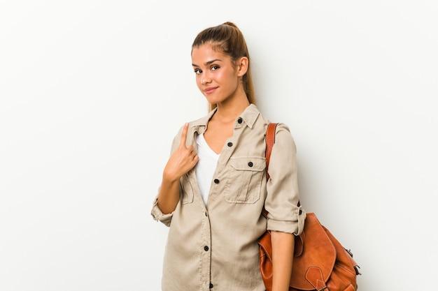 Молодая кавказская женщина готова для путешествия, указывая пальцем на вас