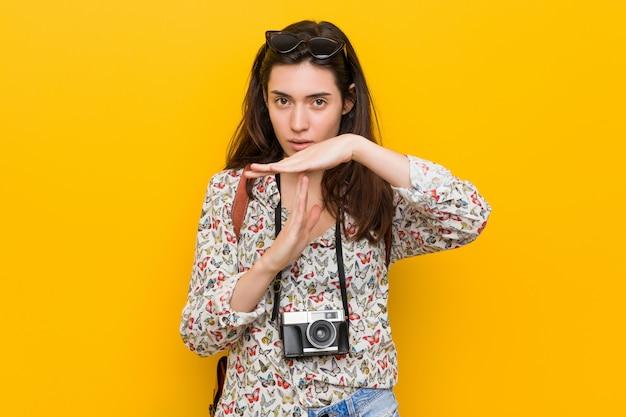 タイムアウトジェスチャーを示す若いブルネット旅行者女性。