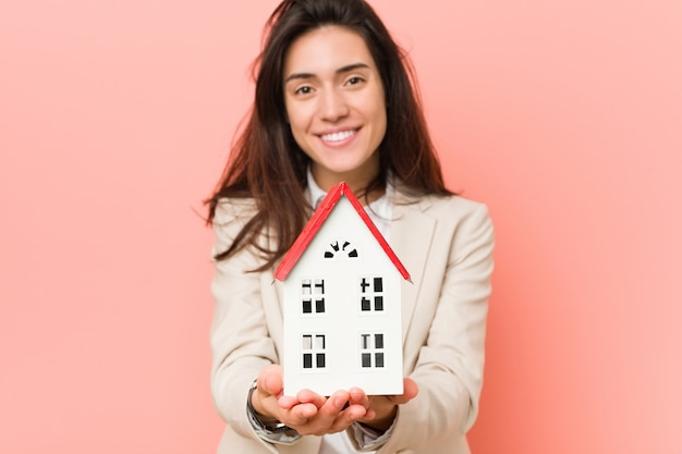 家のモデルを保持している若い白人女性