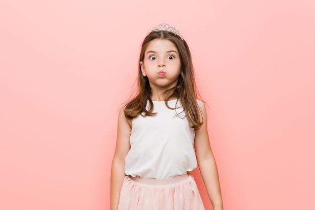 プリンセスルックを着た少女は頬を吹き、疲れた表情をしています
