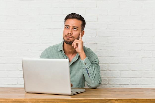 座っている若い男は彼のラップトップでの作業が混乱し、疑わしく不安を感じています。