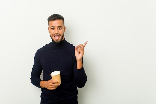 若い人種のアジア人が人差し指で元気に指している笑みを浮かべてテイクアウトコーヒーを保持しています。