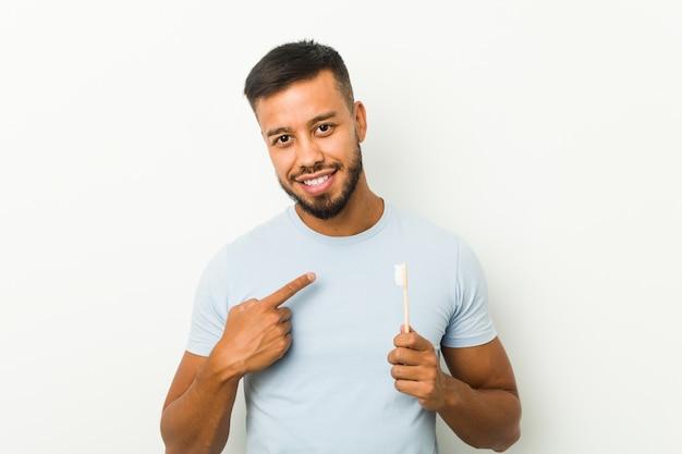 Молодой человек, держащий зубную щетку, указывая пальцем