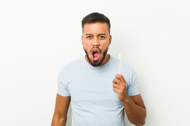 Молодой человек держит зубную щетку кричать очень злой и агрессивный.