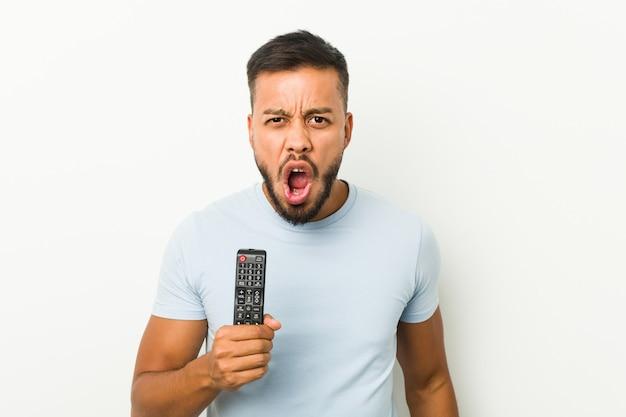 非常に怒っていると攻撃的な叫びテレビコントローラーを保持している若い男。