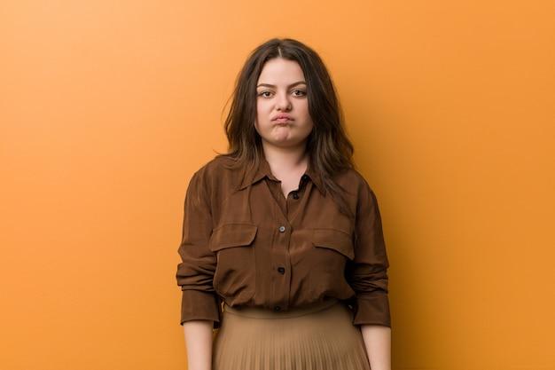 若い女性は頬を吹く、疲れた表情をしています