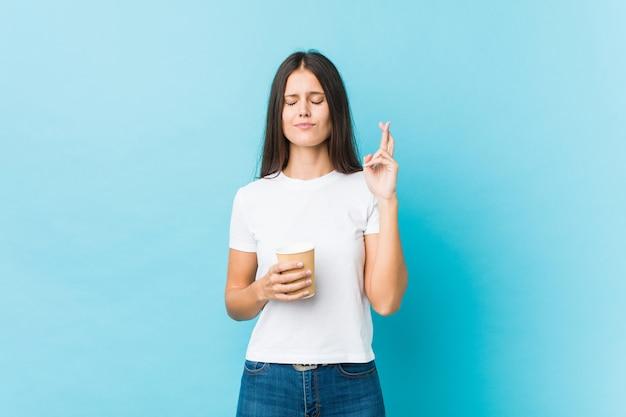 Молодая кавказская женщина держа пальцы скрещивания на вынос кофе для иметь удачу