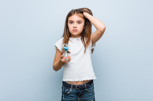 ショックを受けている砂時計を保持している白人少女