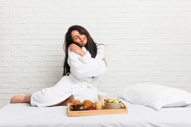 Молодая женщина, принимая завтрак на кровати обнимает, улыбаясь беззаботной и счастливой.