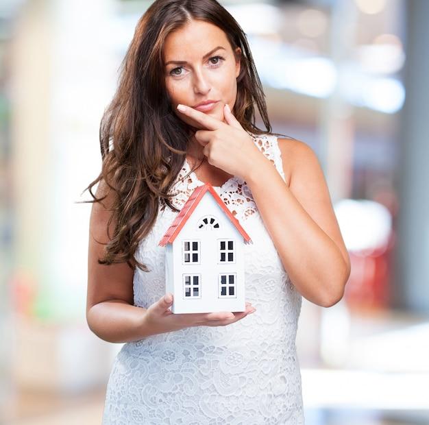 女性の家を保持し、何かを考えます