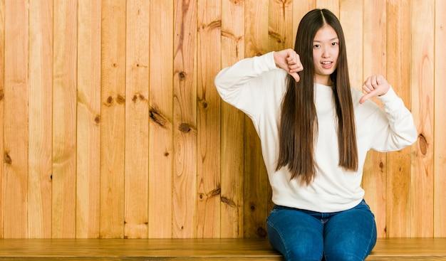親指を示すと嫌悪感を表現する木製の場所に座っている若い中国人女性。