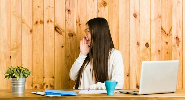 Молодая китайская женщина изучая на ее столе крича и держа ладонь около раскрытого рта.
