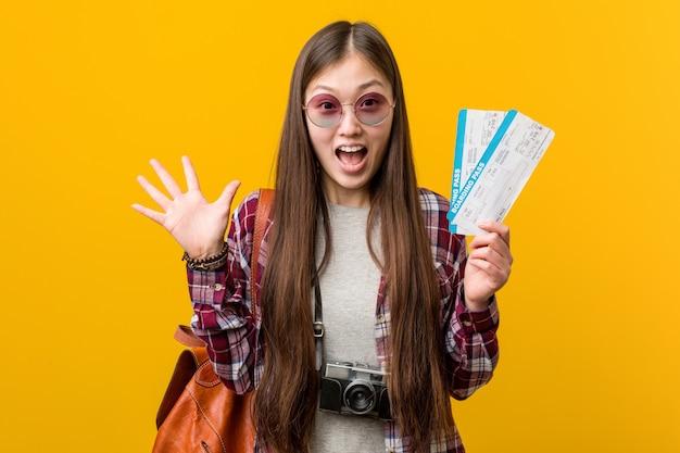 勝利を祝う航空券を保持している若いアジア女性