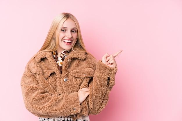人差し指で元気に指している笑顔ピンクの背景にコートを着ている若いブロンドの女性。