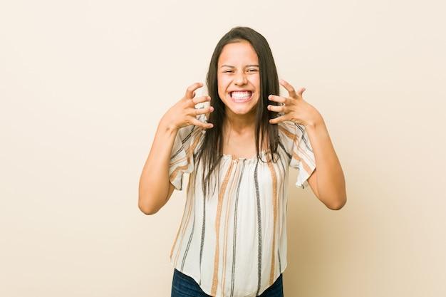 Молодая испанская женщина расстроен, кричать с напряженными руками.
