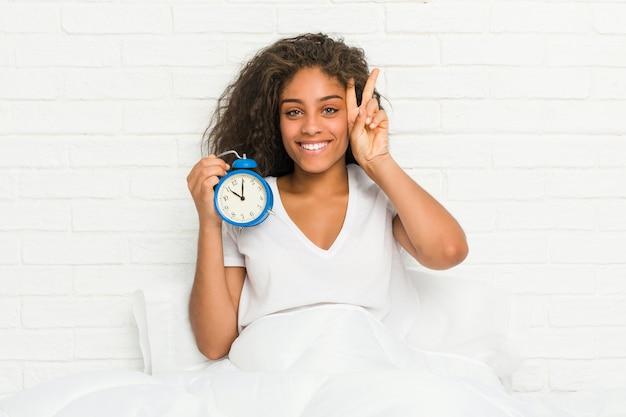 勝利のサインを示し、広く笑顔の目覚まし時計を保持しているベッドに座っている若いアフリカ系アメリカ人女性。