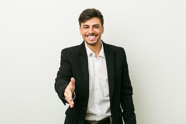 ジェスチャの挨拶でカメラに手を伸ばして若いビジネスヒスパニック男。