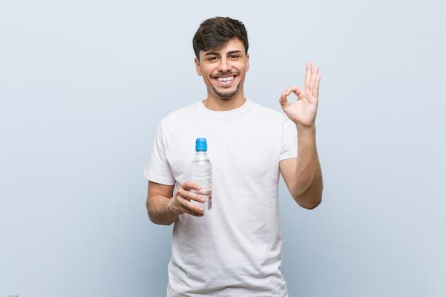Молодой латиноамериканский человек, держащий бутылку с водой, веселый и уверенный, показывая хорошо жест.