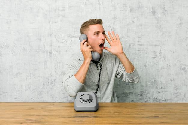 ビンテージ電話で話している若い男が大声で叫ぶ