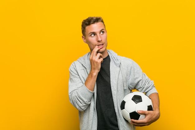 Молодой человек кавказской держа футбольный мяч расслабленно думать о чем-то