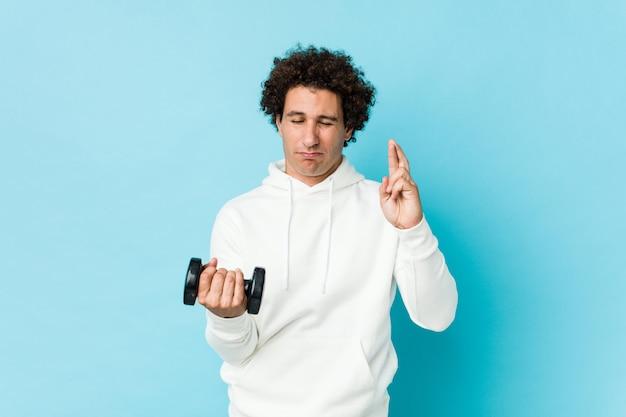 Спортивный человек держит пальцы гантели скрещивания за удачу
