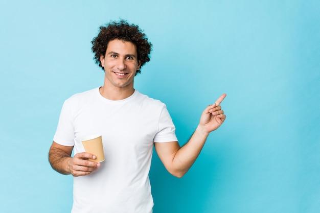 Молодой кавказской кудрявый человек, держа на вынос кофе, улыбаясь, весело указывая с указательный палец прочь.