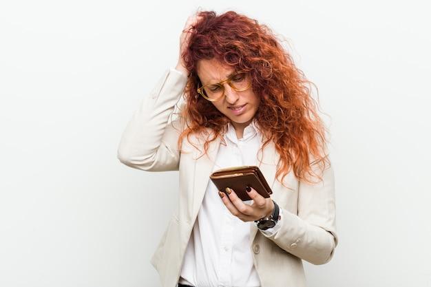ショックを受けている財布を保持している若い白人赤毛の女性、彼女は重要な会議を覚えています。