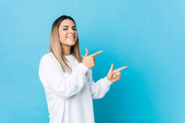 若い白人女性は人差し指を指して興奮しています。