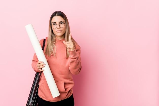 指でナンバーワンを示す建築を勉強している若い女性。