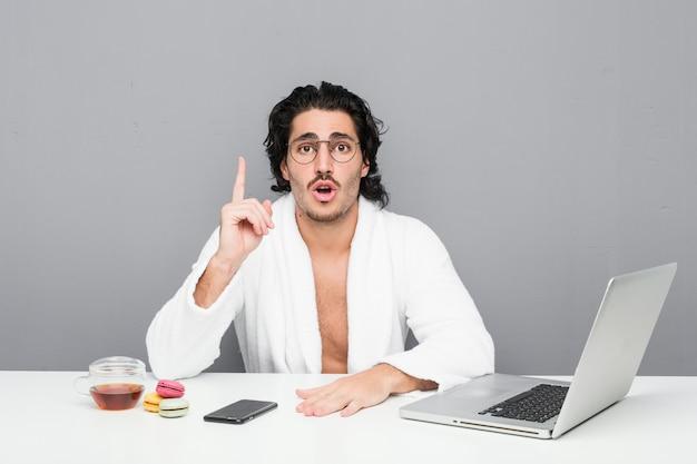 いくつかの素晴らしいアイデア、創造性の概念を持っているシャワーの後に働く若いハンサムな男。