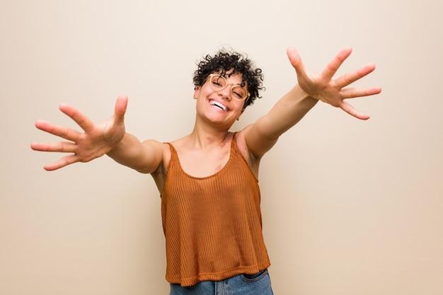 Молодая афро-американская женщина с отметкой дня рождения кожи чувствует уверенно давая объятие к камере.