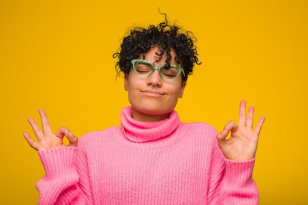 Молодая афро-американская женщина нося розовый свитер ослабляет после тяжелого рабочего дня, она выполняет йогу.