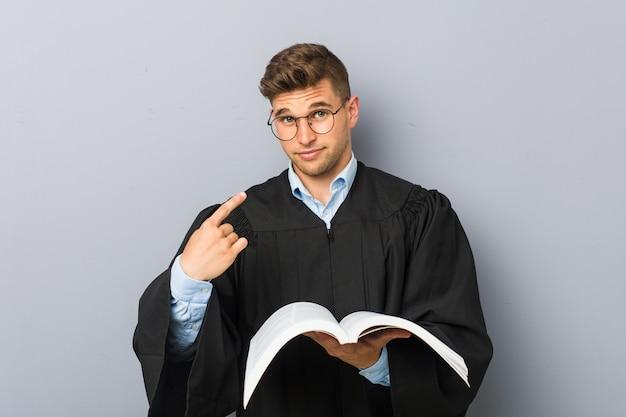 まるで招待が近づくかのようにあなたに指で指している本を保持している若い法学者。