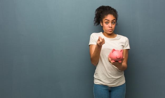 必要なジェスチャーをしている若い黒人女性。彼女は貯金箱を持っています。