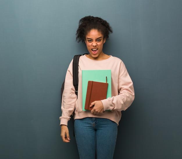 若い学生の黒人女性は非常に怒っていると積極的に叫んでいます。彼女は本を持っています。
